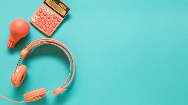 Hoofdtelefoons, calculator en gloeilamp op blauwe achtergrond Gratis Foto