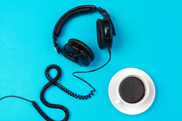 Hoofdtelefoons en koffiekop op blauwe achtergrond, hoogste mening Premium Foto