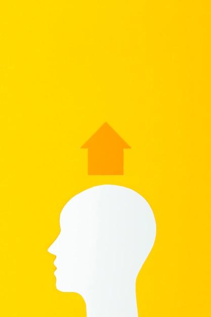 Hoofdvorm met pijl op gele achtergrond Gratis Foto