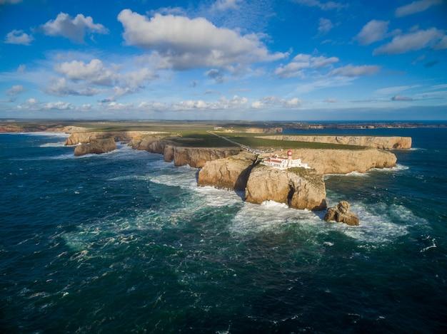 Hoog geschoten landschap van een eiland met een paleis op het omgeven door zee onder een blauwe hemel in portugal Gratis Foto