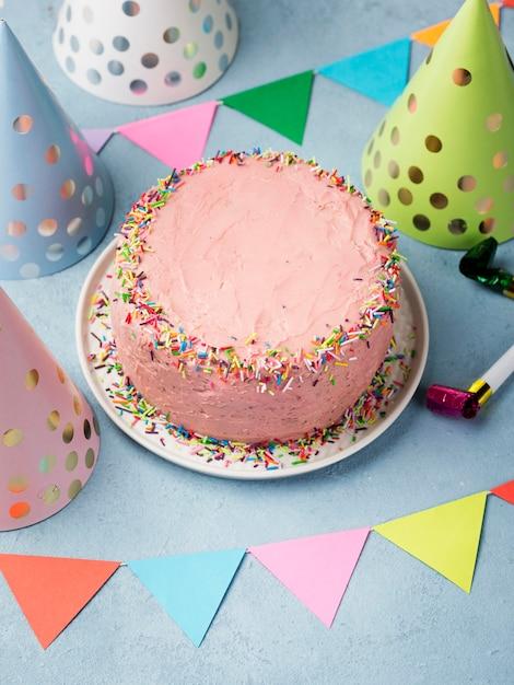 Hoog hoekassortiment met feestmutsen en roze cake Gratis Foto