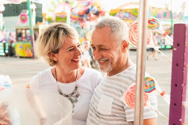 Hoog hoekpaar dat in pretpark glimlacht Gratis Foto