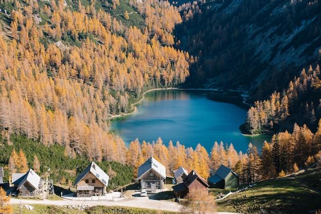 Hoog schot van een klein meer tussen de bergen met een kleine stad in de buurt van de bergbasis Gratis Foto