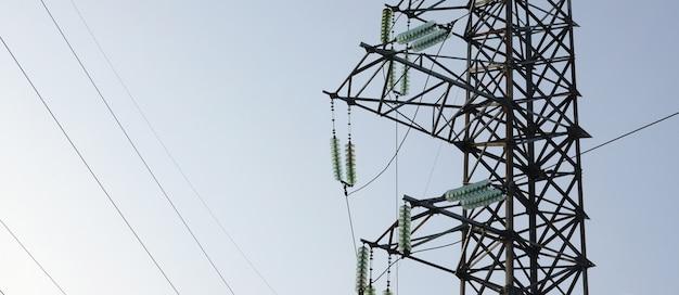Hoogspanningslijnen torenen tegen de blauwe lucht Premium Foto