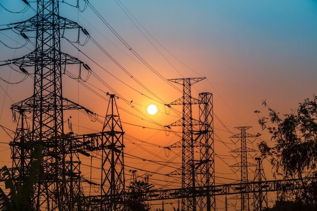Hoogspanningsstalen transmissietoren tijdens zonsondergang Premium Foto