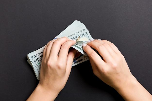 Hoogste mening de handen van een onderneemster die honderd dollarsbankbiljetten tellen op kleurrijk. succes en rijkdom Premium Foto