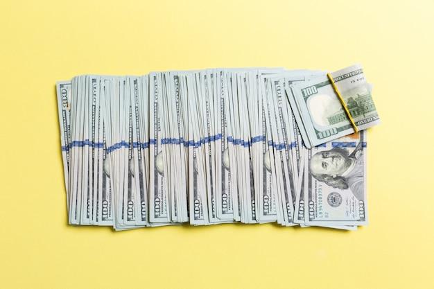 Hoogste mening die van 100 dollarbankbiljetten in één lijn op kleurrijke achtergrond liggen. sluit omhoog van het concept van de geldbesparing Premium Foto