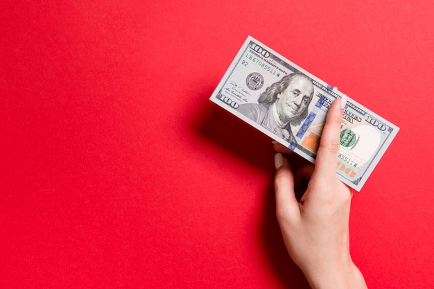 Hoogste mening die van vrouwelijke hand honderd dollarsrekeningen op kleurrijke achtergrond geven Premium Foto