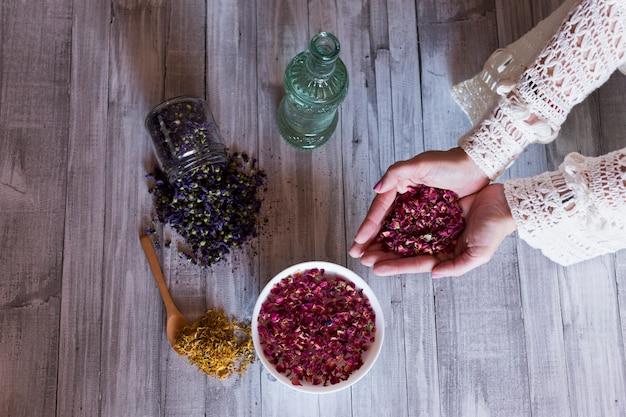 Hoogste mening die van vrouwenhanden droge rozenbladeren houden. gezonde levensstijl concept. binnenshuis. grijze houten tafel achtergrond. gele kurkuma, fles met water en een kom met paarse zaden op tafel. Premium Foto