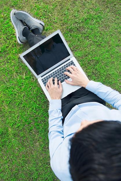 Hoogste mening van aziatische zakenman die laptop voor het werk met behulp van Premium Foto