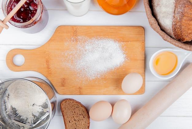 Hoogste mening van bloem op scherpe raad met de melk boterkolf van de aardbeijam en de eieren van roggebrood en deegrol rond op houten achtergrond Gratis Foto