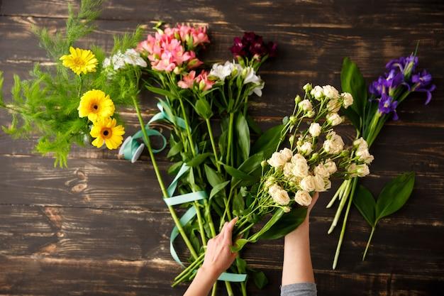Hoogste mening van bloemen, bloemist tijdens het maken van boeket Gratis Foto