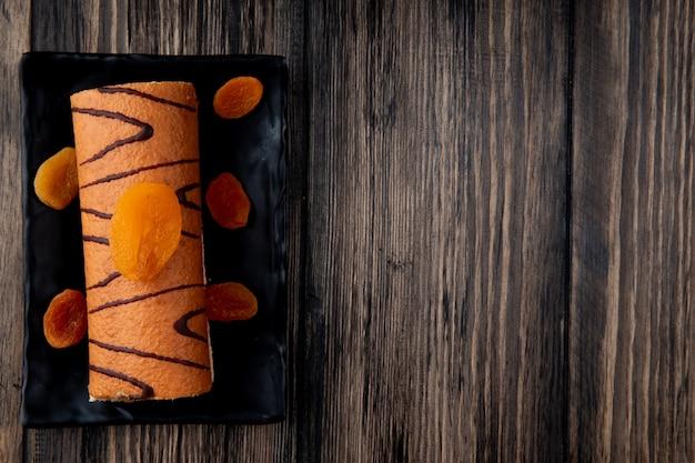 Hoogste mening van broodjescake die met droge abrikozen op een zwart dienblad op rustiek hout met exemplaarruimte wordt verfraaid Gratis Foto