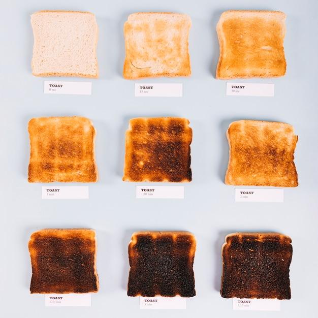 Hoogste mening van broodplakken in verschillende stadia van het roosteren op witte achtergrond Gratis Foto