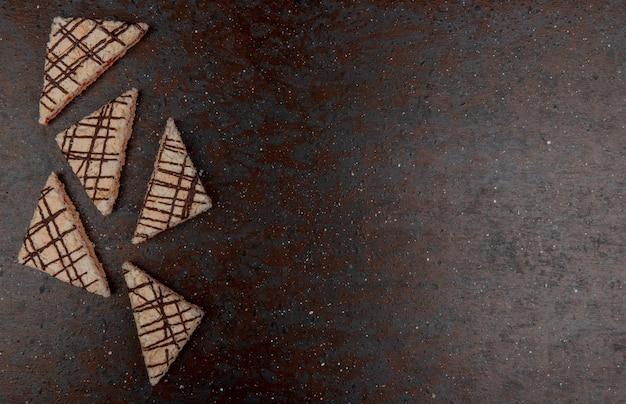 Hoogste mening van cakes op zwarte en kastanjebruine achtergrond met exemplaarruimte Gratis Foto