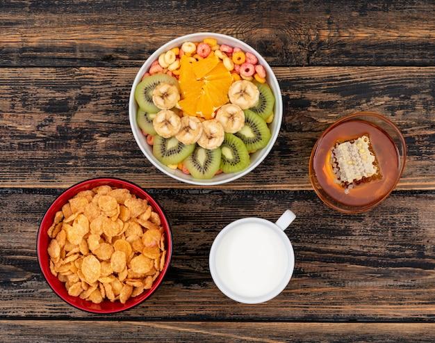 Hoogste mening van cornflakes met vruchten en honing op donkere houten horizontale oppervlakte Gratis Foto