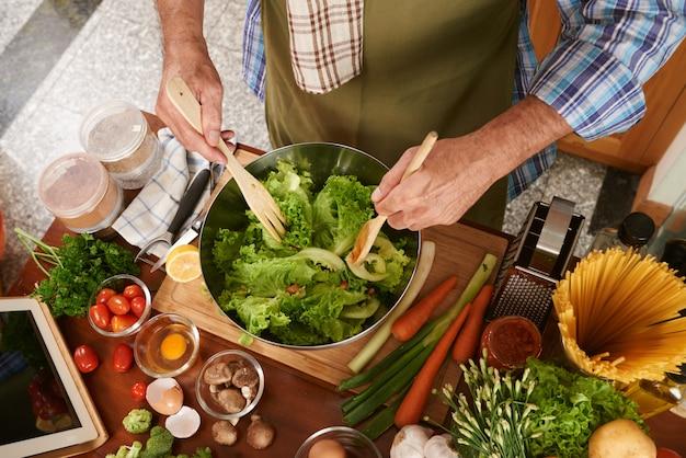 Hoogste mening van de bebouwde mens die in kokschort salade mengen Gratis Foto