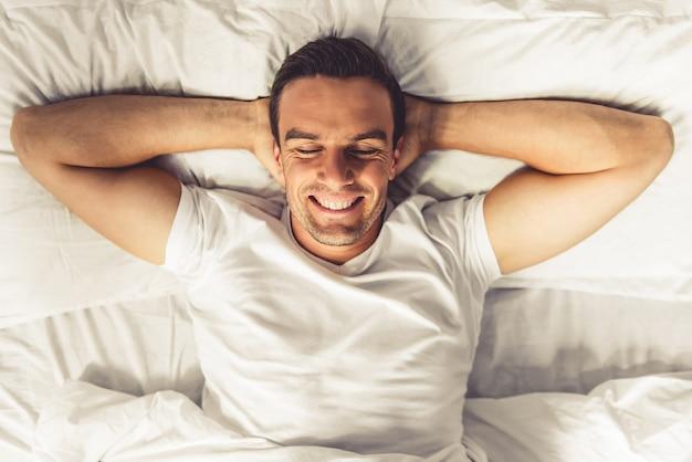 Hoogste mening van de knappe mens die terwijl het liggen glimlacht. Premium Foto