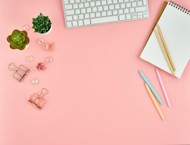Hoogste mening van de moderne roze desktop van het vrouwenbureau met lege blocnote Premium Foto