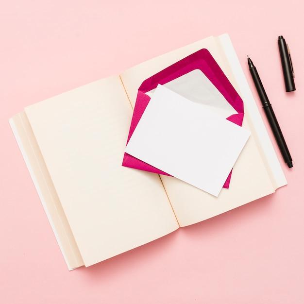 Hoogste mening van een open boek en een envelop Gratis Foto