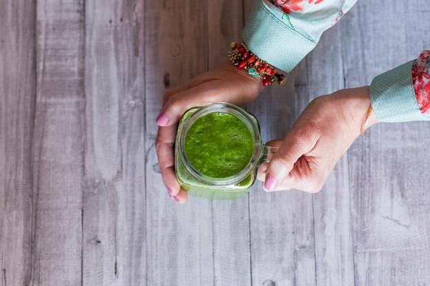 Hoogste mening van een vrouw die een kruik met groen detoxsap houdt. grijze houten tafel achtergrond. natuurlijk en gezond concept Premium Foto