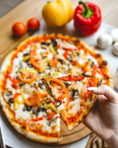 Hoogste mening van een vrouwelijke hand die een stuk van pizza met de tomaten en de kaas van paddestoelengroene paprika's op houten lijstachtergrond houden Gratis Foto