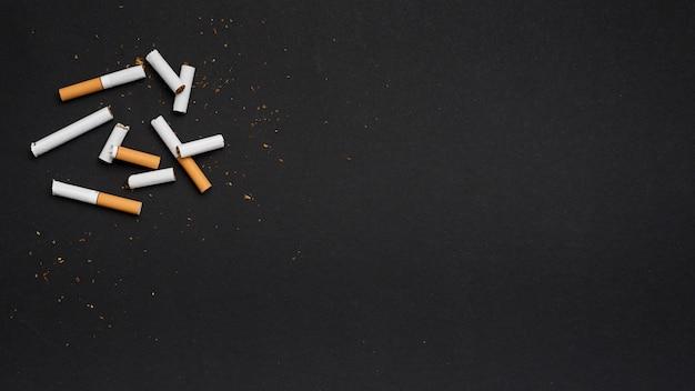 Hoogste mening van gebroken sigaret met tabak op zwarte achtergrond Gratis Foto