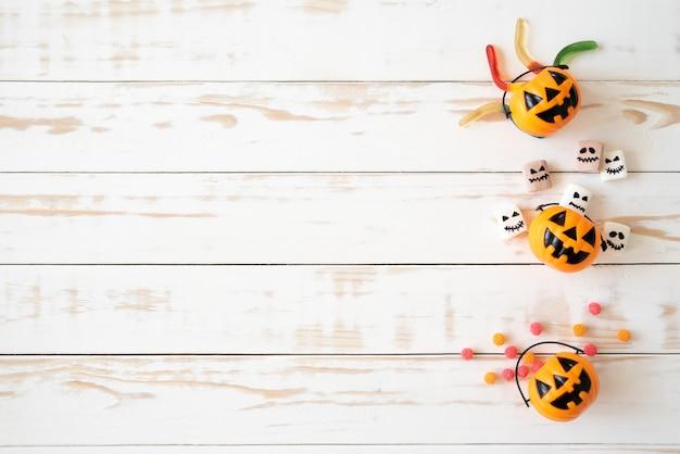 Hoogste mening van gele spookpompoenen met geleiworm op houten achtergrond. halloween concept. Premium Foto
