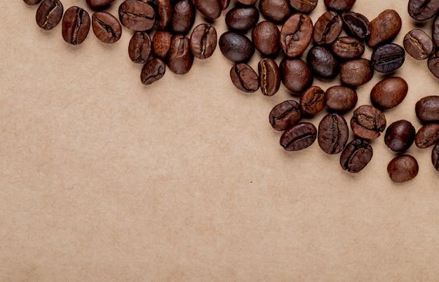 Hoogste mening van geroosterde koffiebonen die op de achtergrond van de pakpapiertextuur worden verspreid met exemplaarruimte Gratis Foto