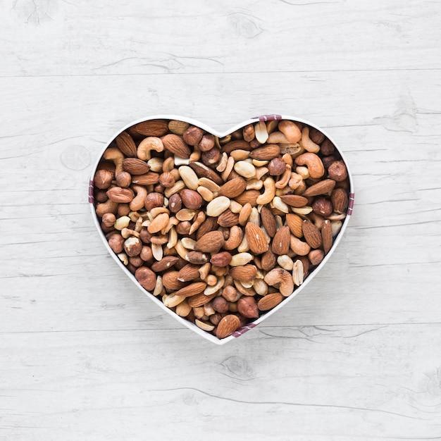 Hoogste mening van gezonde dryfruits in hartvorm op houten bureau Gratis Foto
