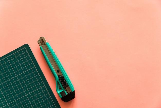 Hoogste mening van groene rubber scherpe mat met groene snijder aan de linkerkant over roze kleurendocument achtergrond. achtergrond met kopie ruimte. Premium Foto