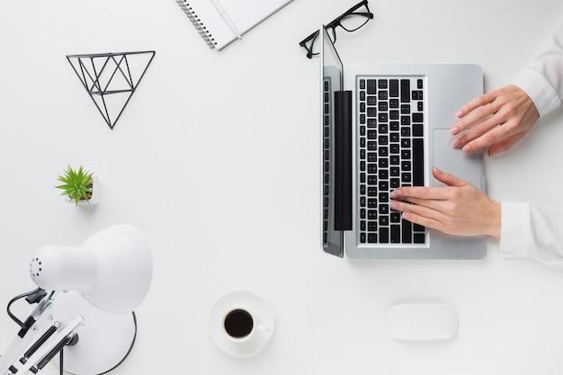 Hoogste mening van handen die aan laptop op bureau werken Gratis Foto