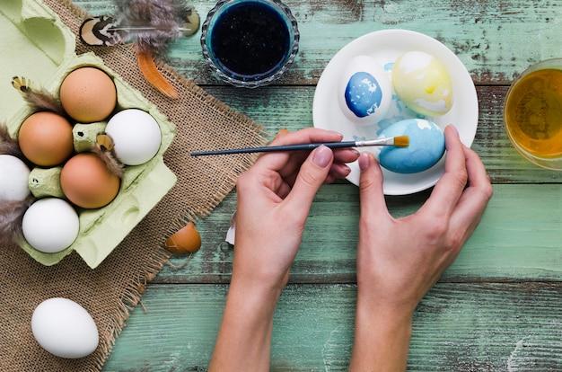 Hoogste mening van handen die eieren schilderen voor pasen Gratis Foto