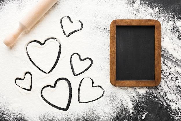 Hoogste mening van hartvormen in bloem met bord Gratis Foto