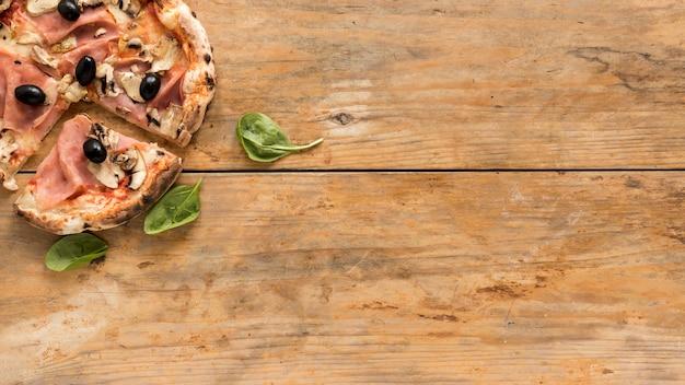 Hoogste mening van heerlijke pizza met basilicumblad over houten bureau Gratis Foto