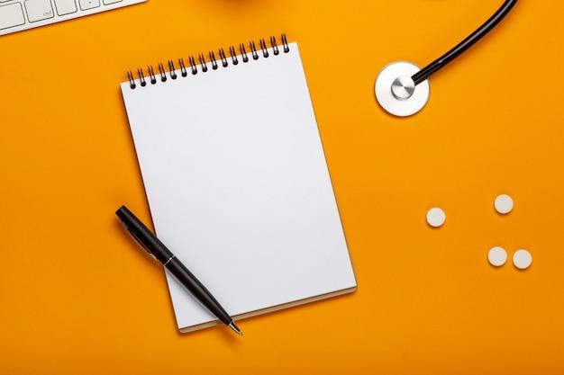 Hoogste mening van het bureau van de arts met de blocnote van het stethotoetsenbord en pen, voorschrift en pillen Premium Foto