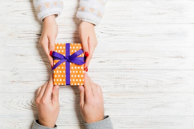 Hoogste mening van het houden van een gift in vrouwelijke en mannelijke handen op houten. Premium Foto