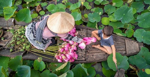 Hoogste mening van het vietnamese jongen spelen met mamma over de traditionele houten boot Premium Foto