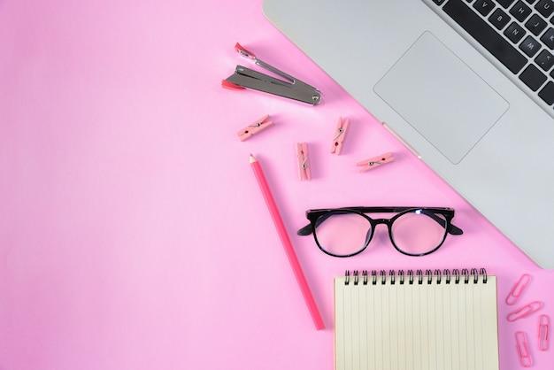 Hoogste mening van kantoorbehoeften of schoollevering met boeken, kleurenpotloden, laptop, klemmen en glazen op roze achtergrond met copyspace. onderwijs of terug naar school-concept. Premium Foto