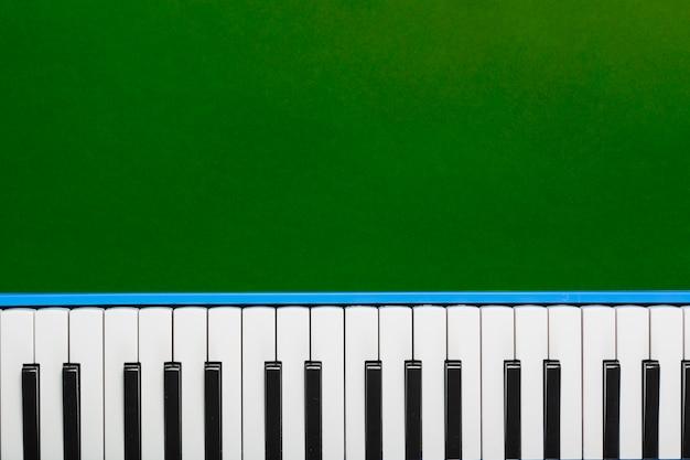 Hoogste mening van klassiek piano zwart-wit toetsenbord op groene achtergrond Premium Foto