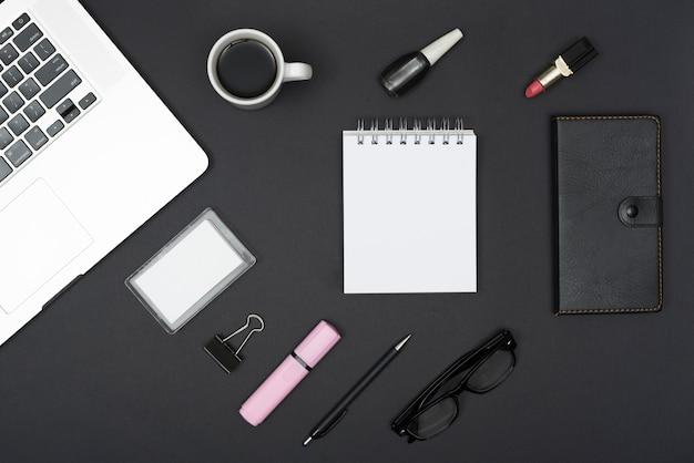 Hoogste mening van laptop met koffiekop; lippenstift; nagellak en office-spullen tegen zwarte achtergrond Gratis Foto