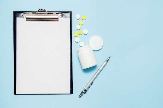 Hoogste mening van leeg document voor het schrijven van artsenvoorschrift. pillen op blauw Premium Foto
