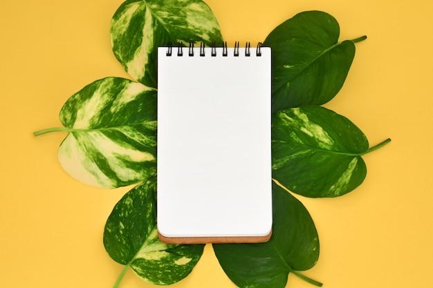 Hoogste mening van leeg geopend leeg notitieboekje op gouden pothos-bladeren Premium Foto