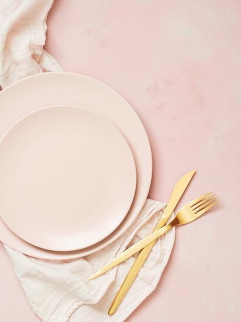 Hoogste mening van lege ceramische platen en gouden bestek op pastelkleur roze achtergrond Premium Foto