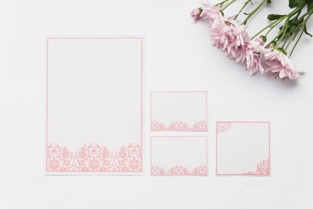 Hoogste mening van lege kaarten en roze bloemen op witte achtergrond Gratis Foto