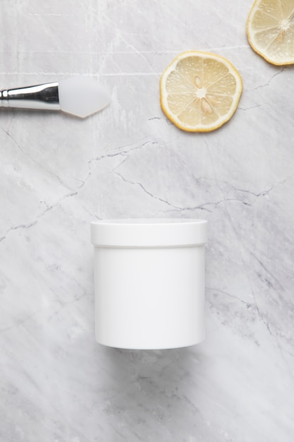 Hoogste mening van roomborstel en citroenplakken op marmeren achtergrond Gratis Foto