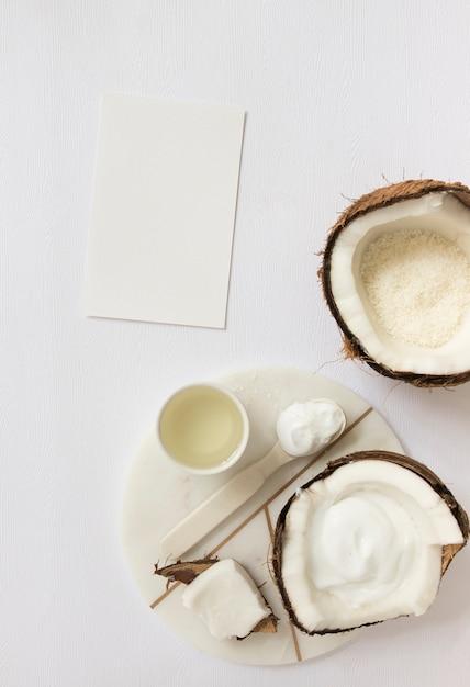 Hoogste mening van schoonheidsmiddel met kokosnoot en lege kaart op witte oppervlakte Gratis Foto