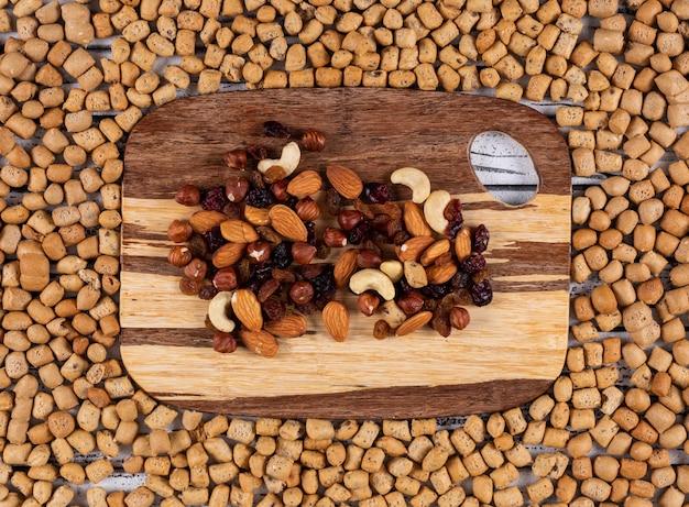 Hoogste mening van snacks als noten, droge vruchten op scherpe raad op horizontale crackerstextuur Gratis Foto