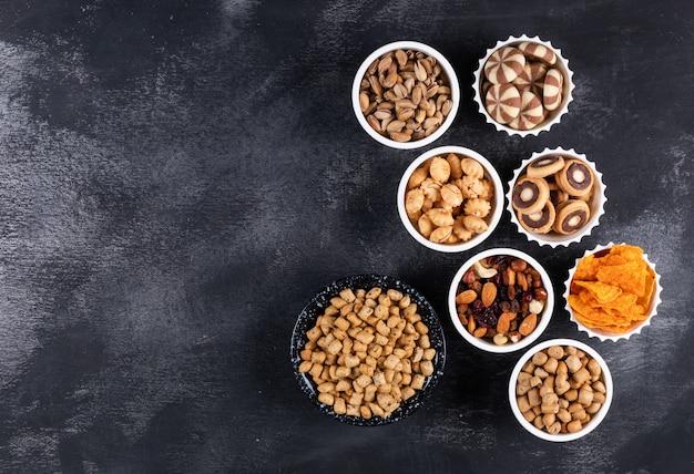 Hoogste mening van verschillend soort snacks als noten, crackers en koekjes in kommen met horizontale exemplaarruimte op donkere horizontale achtergrond Gratis Foto