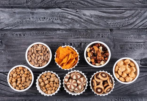 Hoogste mening van verschillend soort snacks als noten, crackers en koekjes in kommen met horizontale exemplaarruimte op donkere horizontale oppervlakte Gratis Foto